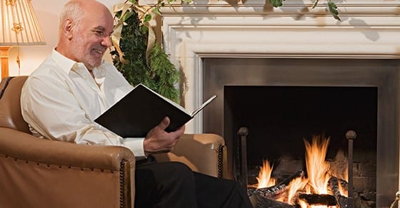 Man reading by fire place