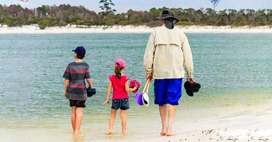 grandfather walking on beach with grandkids | taxes and retiring and moving to another state | Dalby Wendland & Co | CPAs | Business Advisors | Colorado