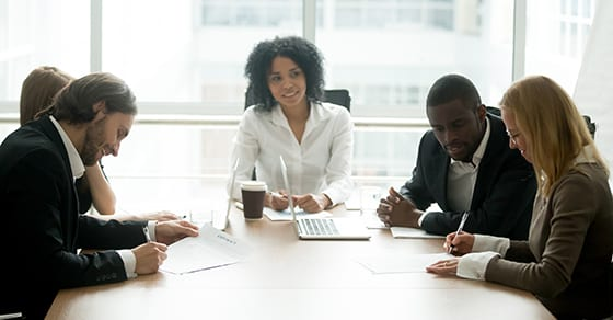 business people working around conference table | buy-sell agreement | Dalby Wendland & Co. | CPAs | Business Advisors | Grand Junction CO | Glenwood Springs CO | Montrose CO