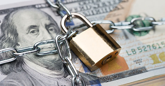 Closeup of metallic chain and padlock around dollar bundle | Reporting Restricted Cash | Dalby Wendland & Co. | CPAs & Business Advisors | Grand Junction CO | Glenwood Springs CO | Montrose CO