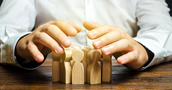 protective hands hovering above wood people cutouts | American Rescue Plan Act Extends Employee Retention Credit | Dalby Wendland & Co. | CPAs & Business Advisors | Grand Junction CO | Glenwood Springs CO | Montrose CO