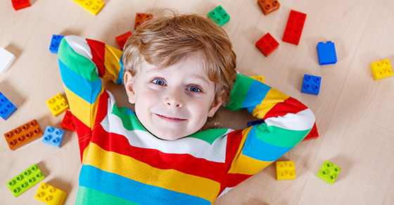 a smiling toddler boy laying on his back with toys scattered around him | Dalby Wendland & Co. | CPAs & Business Advisors | Grand Junction CO | Glenwood Springs CO | Montrose CO