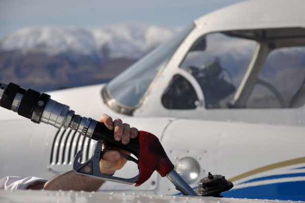 person fueling up a small airplane with Colorado mountains in the background