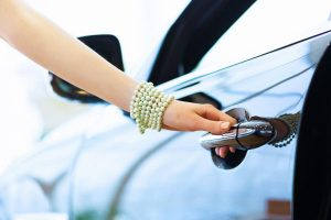 woman's hand opening a vehicle handle in car showroom