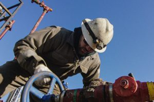 oil and gas employee working on large pipe
