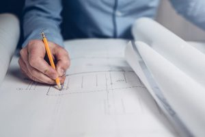 architect drawing building plans with a pencil