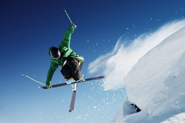 extreme skier jumping off ledge of snow