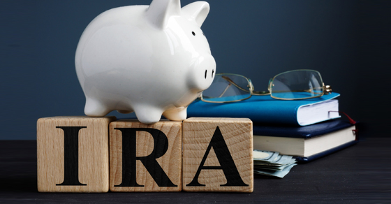 piggy bank standing on wood blocks that spell out IRA on table with books and reading glasses | spousal rollover IRA | Dalby Wendland & Co. | CPAs & Business Advisors | Grand Junction CO | Glenwood Springs CO | Montrose CO