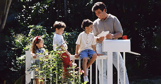 father with children outside getting mail