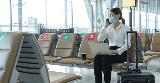 business woman in airport wearing mask | how to properly report business-related travel and entertainment expenses | Dalby Wendland & Co. | CPAs & Business Advisors | Grand Junction CO | Glenwood Springs CO | Montrose CO