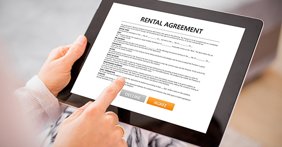 person electronically signing a rental agreement on a tablet